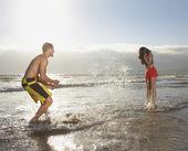 Paar spetteren in water op strand — Stockfoto