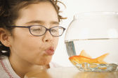 Young girl making a kissy face for a goldfish — Stock Photo