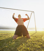 Goalie kneeling with hands above head — Stock Photo