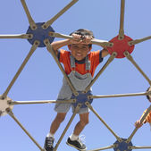 Young boy playing on a play structure — Stockfoto