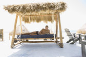 Bare chested man reading on a hammock at the beach — Stock Photo