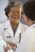 Kobieta lekarz śmiejąc się z lekarza — Zdjęcie stockowe