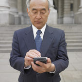 Senior Asian businessman using electronic organizer — Stock Photo