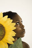 Young woman holding a sunflower by her face — Stock Photo