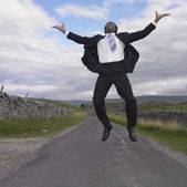 Businessman jumping for joy in rural location — Stock Photo