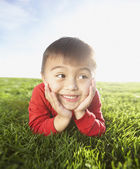 Portrait of young boy laying in grass with head resting in hands — Stock Photo
