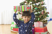 Little boy holding Christmas presents on his head — Stock Photo