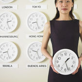 Businesswoman holding clock with time zone clocks on the wall behind him — Stock Photo