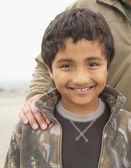 Portrait of boy smiling with father's hand on his shoulder — Stock Photo