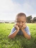 Portrait of boy laying in grass with head resting on hands — Stock Photo