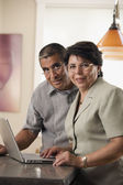 Portrait of mature couple with laptop — Stock Photo