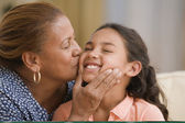 Mother kissing her daughter's cheek — Stock Photo