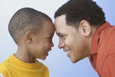 Close up of father and young son looking at each other — Stock Photo