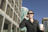 Businesswoman wearing sunglasses talking on cell phone with coffee — Stock Photo