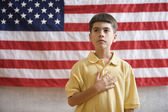 Boy in front of American flag with hand over heart — Stock Photo