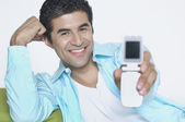 Young man showing off his cell phone — Stock Photo
