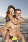 Man giving woman piggy back ride at beach — Stock Photo