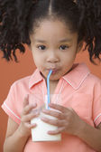 Portrait of Asian girl with ponytails drinking milk with straw — Stock Photo
