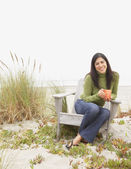 Portrait of woman sitting in chair with coffee at beach — Stock Photo