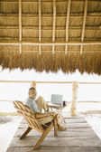 Young man using a laptop underneath thatch roof on the beach — Стоковое фото