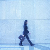 Blurred image of businesswoman walking — Stock Photo