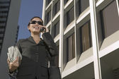 Businesswoman wearing sunglasses talking on cell phone — Stock Photo