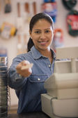Female cashier handing the camera its credit card — Stock Photo