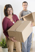 Portrait of couple carrying boxes — Stock Photo