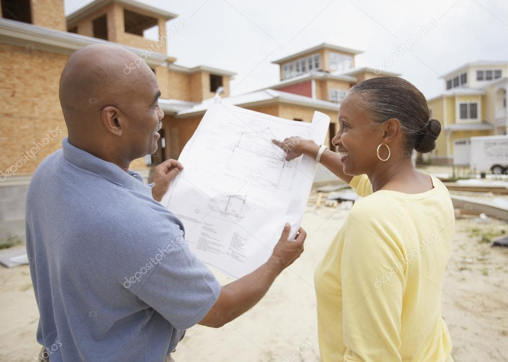 African american couple reading house plans at for How to read construction site plans