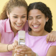 Two teenage girls text messaging on cell phone — Stock Photo