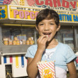 Young girl eating popcorn at a carnival — Stock Photo