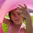 Portrait of girl looking through inner tube - Stock Photo