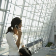 Businesswoman talking on cell phone in airport — Stock Photo #23240166