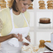Woman decorating cake at bakery — Stock Photo