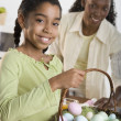 Portrait of girl holding Easter eggs in basket with mother looking at her — Stock Photo