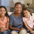 Mother and daughters smiling for the camera together — Stock Photo #23240280