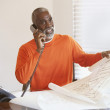 Senior man talking on phone while looking at plans — Stock Photo