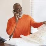 Senior man talking on phone while looking at plans — Stock Photo