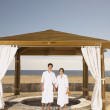 Couple in bathrobes outdoors at beach resort — Stock Photo