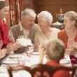 Stock Photo: Grandmother with birthday cake and family at dinner table