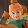 Young Hispanic child in pumpkin costume with pumpkins — Stock Photo