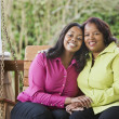 Stock Photo: Mother and daughter smiling on porch swing