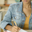Female Dominican teenager writing in her notebook in classroom — Foto de Stock