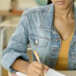 Stock Photo: Female Dominican teenager writing in her notebook in classroom
