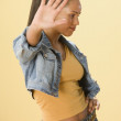 Studio shot of a female Dominican teenager holding out the palm of her hand — Stockfoto