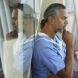 Middle-aged male African surgeon thinking — Stock Photo