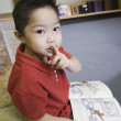 Stock Photo: Young boy gesturing for silence in library