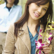 Young woman posing for the camera with flowers — Stock Photo