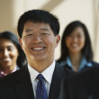 Asian businessman with co-workers in the background — Foto de Stock