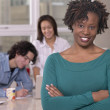 African businesswoman with co-workers in the background — Stock Photo